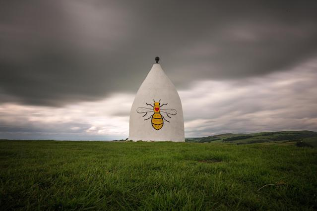 <p>A worker bee adorns the side of Bollington White Nancy to remember those killed and injured in the Manchester Arena attack, on May 30, 2017 in Macclesfield, England. White Nancy overlooks the hills and countryside in East Chesire with views across the plain to Manchester and can be seen for miles. White Nancy was built in 1815 as a summer house, and memorial to the the battle of Waterloo. An explosion occurred at Manchester Arena on the evening of May 22, Killing 22 and injuring many more. (Christopher Furlong/Getty Images) </p>
