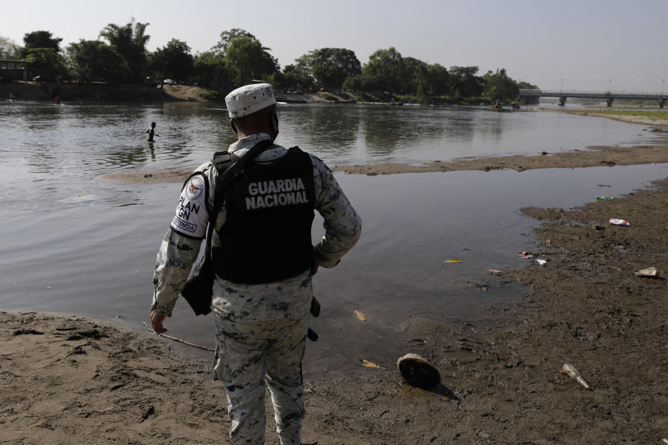 A Mexican National Guard stands on the bank of the Suchiate River, the natural border with Guatemala and Mexico, near Ciudad Hidalgo, Mexico, Sunday, March 21, 2021. Mexico has sent hundreds of immigration agents, police and National Guard to its southern border to launch an operation to crack down on migrant smuggling. (AP Photo/Eduardo Verdugo)