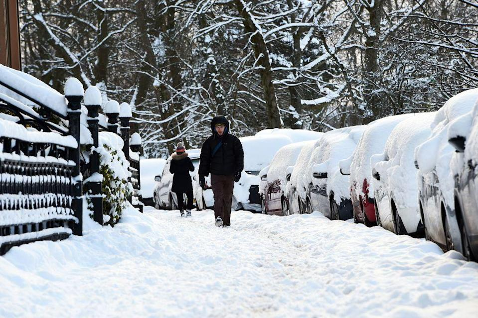 <p>Commuters walk to work along empty streets in Glasgow, where flights have been cancelled and trains delayed due to the weather conditions. (Getty) </p>