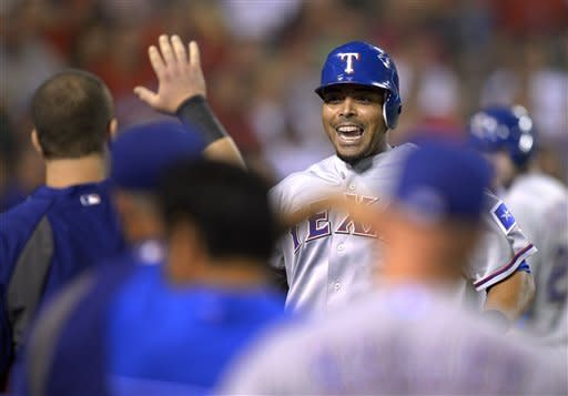 Texas Rangers' Nelson Cruz celebrates with teammates after scoring on a sacrifice fly by Geovany Soto during the fifth inning of the Rangers' baseball game against the Los Angeles Angels, Thursday, Sept. 20, 2012, in Anaheim, Calif. (AP Photo/Mark J. Terrill)