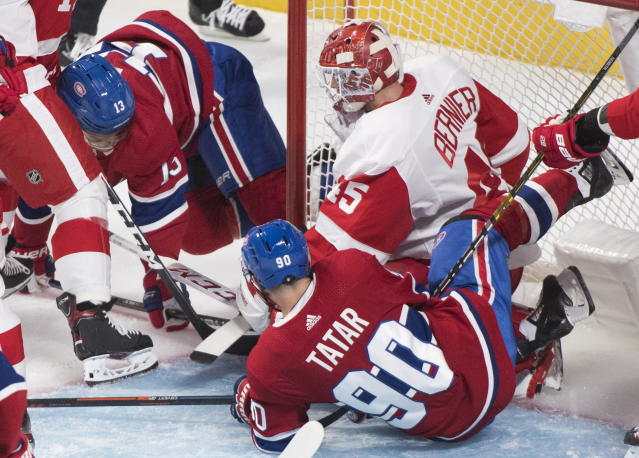Montreal Canadiens' Max Domi (13) scores against Detroit Red Wings goaltender Jonathan Bernier as Canadiens' Tomas Tatar looks for a rebound during second-period NHL hockey game action in Montreal, Thursday, Oct. 10, 2019. (Graham Hughes/The Canadian Press via AP)