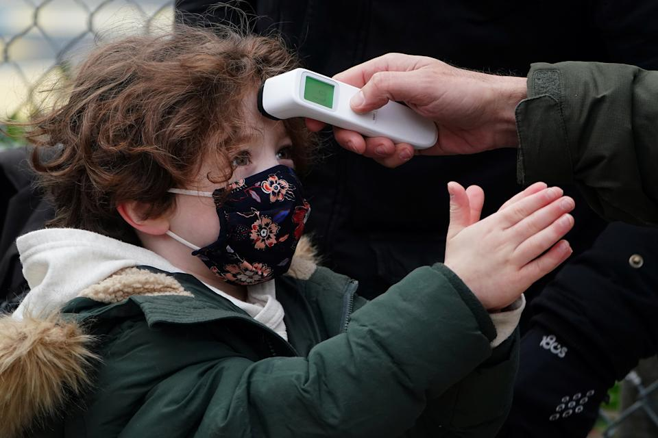 A child has his temperature checked as he rubs his hands with hand sanitizer before attending class at PS 361 on the first day of a return to class during the coronavirus disease (COVID-19) pandemic in the Manhattan borough of New York City, New York, U.S., December 7, 2020. REUTERS/Carlo Allegri