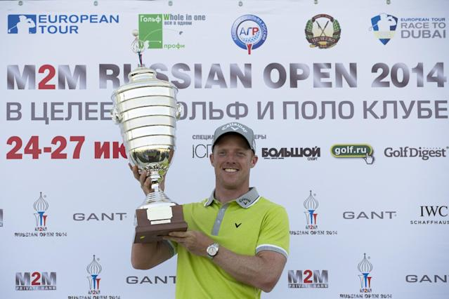 Britain's David Horsey holds his trophy after the winning in the final round at the M2M Russian Open golf tournament at Tseleevo Golf and Polo Club outside Moscow, Russia, Sunday, July 27, 2014. Horsey sensationally forced and won a play-off with Damien McGrane to take the M2M Russian Open at Tseleevo Golf & Polo Club.(AP Photo/Alexander Zemlianichenko)