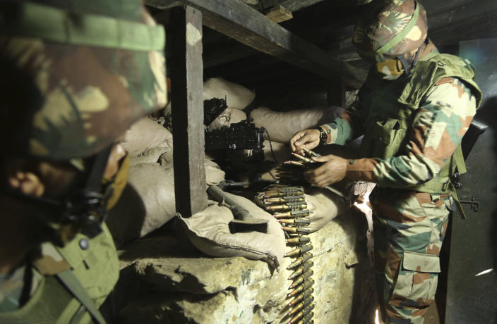 Indian army soldiers prepare a light machine gun in their bunker at a forward post along the Line of Control (LOC) between India and Pakistan border in Poonch, about 250 kilometers (156 miles) from Jammu, India, Friday, Dec. 18, 2020. Tens of thousands of soldiers from India and Pakistan are positioned along the two sides. The apparent calm is often broken by the boom of blazing guns, with each side accusing the other of initiating the firing. (AP Photo/Channi Anand)