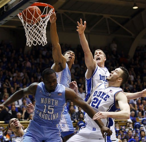 North Carolina's James Michael McAdoo dunks past Duke's Mason Plumlee, rear, and Miles Plumlee (21) and North Carolina's P.J. Hairston (15) during the first half of an NCAA college basketball game in Durham, N.C., Saturday, March 3, 2012. (AP Photo/Gerry Broome)