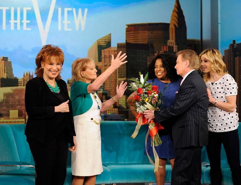 """This image released by ABC shows Barbara Walters, second left, receiving flowers from Regis Philbin, second right, on her first day back to """"The View,"""" in New York on Monday, March 4, 2013, after being sidelined for six weeks by chickenpox and a concussion. Looking on are co-hosts Joy Behar, left, Sherri Shepherd and Elisabeth Hasselbeck, right. (AP Photo/ABC, Donna Svennevik)"""