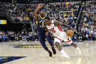 Miami Heat guard Kendrick Nunn (25) drives around Indiana Pacers guard Aaron Holiday (3) during the first half of an NBA basketball game in Indianapolis, Wednesday, Jan. 8, 2020. (AP Photo/AJ Mast)