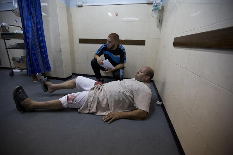 A wounded Palestinian man waits for treatment on the ground in the al-Shifa hospital after an Israeli air strike on Gaza City on August 22, 2014 (AFP Photo/Mahmud Hams)