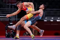 <p>Iran's Mohammadreza Geraei (blue) wrestles Colombia's Julian Stiven Horta Acevedo in their men's greco-roman 67kg wrestling early round match during the Tokyo 2020 Olympic Games at the Makuhari Messe in Tokyo on August 3, 2021. (Photo by Jack GUEZ / AFP)</p>