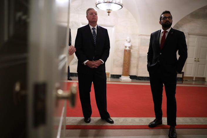 """<p>US Senator Lindsey Graham (left) and Kashyap """"Kash"""" Pramod Patel (right) listen as Donald Trump makes a statement in the White House on October 27, 2019</p> (Getty Images)"""