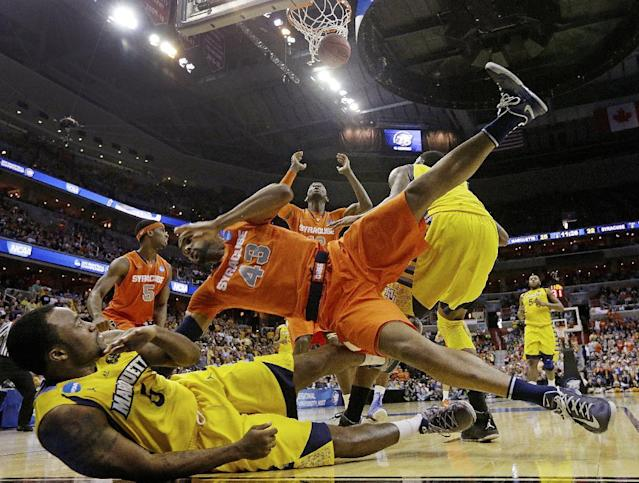 Syracuse forward James Southerland (43) lands on Marquette guard Junior Cadougan (5) as Syracuse center Baye Keita (12) looks for the rebound during the second half of the East Regional final in the NCAA men's college basketball tournament, Saturday, March 30, 2013, in Washington. (AP Photo/Pablo Martinez Monsivais)