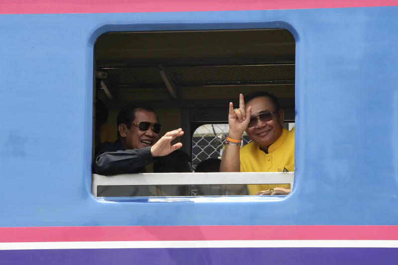 In this photo released by the Government Spokesman's Office, Cambodian's Prime Minister Hun Sen, left, and Thailand's Prime Minister Prayuth Chan-ocha wave from a window on a train at the Thai-Cambodian border town of Aranyaprathet, Thailand, Monday, April 22, 2019. The leaders have met to mark the ceremonial reopening of a rail link that will restore rail service between the two countries after more than four decades. (Government Spokesman Office via AP)