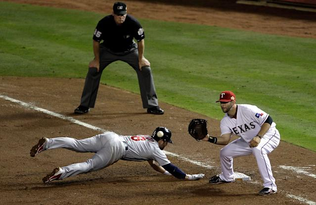 ARLINGTON, TX - OCTOBER 23: Nick Punto #8 of the St. Louis Cardinals dives safely back to first base before the tag by Mitch Moreland #18 of the Texas Rangers in the sixth inning during Game Four of the MLB World Series at Rangers Ballpark in Arlington on October 23, 2011 in Arlington, Texas. (Photo by Rob Carr/Getty Images)