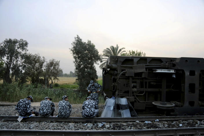 Egyptian security forces prepare to break their fast during the holy month of Ramadan, at the site of a passenger train that derailed injuring around 100 people, near Banha, Qalyubia province, Egypt, Sunday, April 18, 2021. The train was travelling to the Nile Delta city of Mansoura from the Egyptian capital, the statement said. (AP Photo/Fadel Dawood)
