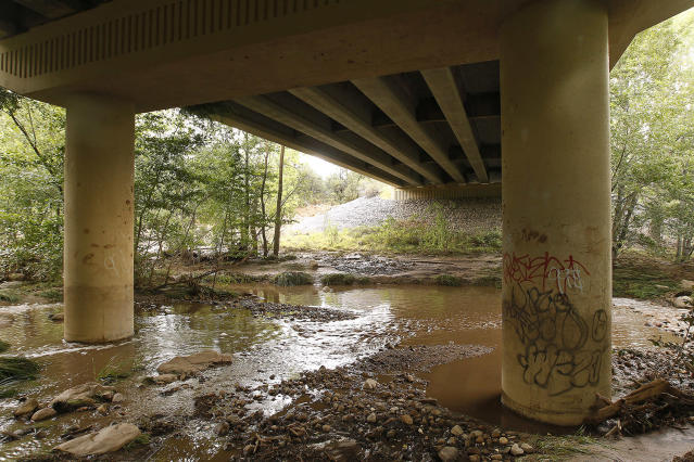 <p>Muddy floodwaters of the East Verde River flow under a bridge were at least one victim of a flash flood was found during a search and rescue operation by the Gila County Sheriff's Office on Sunday, July 16, 2017, in Payson, Ariz. (AP Photo/Ralph Freso) </p>