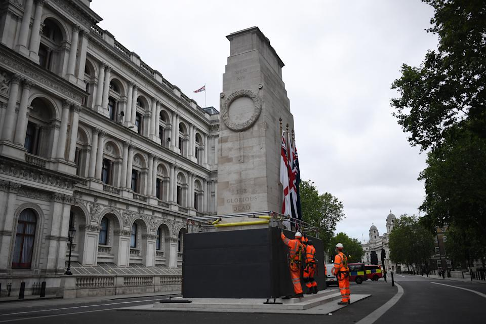 """LONDON, ENGLAND - JUNE 11: Workers erect a protective barrier around the Cenotaph in anticipation of protests tomorrow on June 11, 2020 in London, England. Outside the Houses of Parliament, the statue of former Prime Minister Winston Churchill was spray-painted with the words """"was a racist"""" amid anti-racism protests over the weekend. In Bristol, protesters toppled a statue of Edward Colston, a 17th-century slave-trader, and tossed it into the harbor. (Photo by Peter Summers/Getty Images)"""