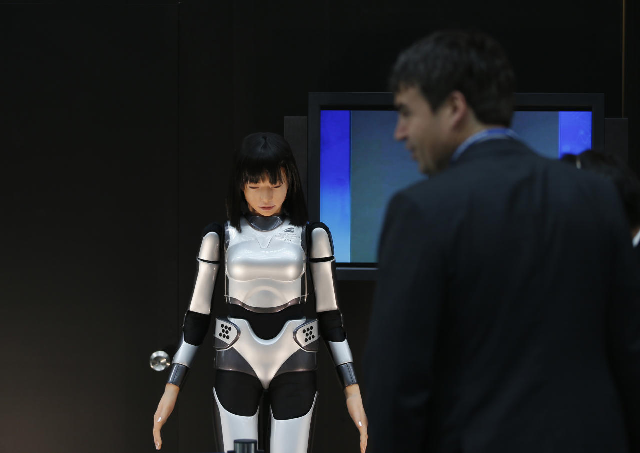A man looks at the HRP-4C Miim humanoid robot at the venue of the Annual Meetings of the International Monetary Fund and the World Bank Group in Tokyo October 9, 2012. Global growth in advanced economies is too weak to bring down unemployment and what little momentum exists is coming primarily from central banks, the International Monetary Fund said in its World Economic Outlook, released ahead of its twice-yearly meeting, which will be held in Tokyo later this week.   REUTERS/Toru Hanai (JAPAN - Tags: POLITICS BUSINESS)
