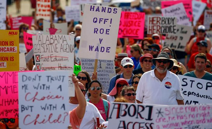 Protesters for women's rights march to the Alabama Capitol to protest a law passed last week making abortion a felony in nearly all cases with no exceptions for cases of rape or incest, Sunday, May 19, 2019, in Montgomery, Ala. (AP Photo/Butch Dill)