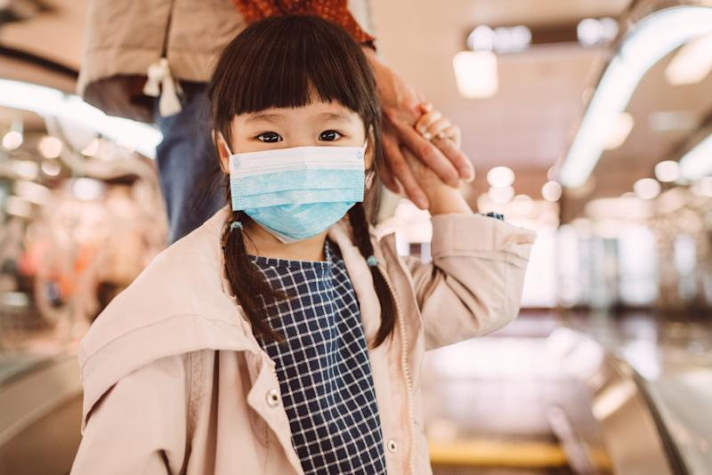 Lovely little girl with medical face mask holding her mom's hand, looking at the camera while standing on the ascending escalator in the shopping mall