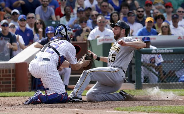 Chicago Cubs catcher John Baker, left, tags out Pittsburgh Pirates' Ike Davis at home plate during the second inning of a baseball game Friday, June 20, 2014, in Chicago. The play was upheld on video review. (AP Photo/Charles Rex Arbogast)
