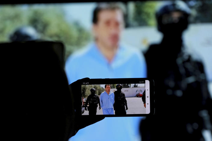 Bassem Awadallah, one of two former officials accused of helping Jordanian Prince Hamzah try to overthrow his half-brother King Abdullah II, appears on a mobile phone screen as he is escorted by security personnel at a state security court, in Amman, Jordan, Monday, July 12, 2021. The court sentenced the two to 15 years in prison. Awadallah, who has U.S. citizenship and once served as a top aide to King Abdullah II, and Sharif Hassan bin Zaid, a member of the royal family, were found guilty of sedition and incitement charges. (AP Photo/Raad Adayleh)
