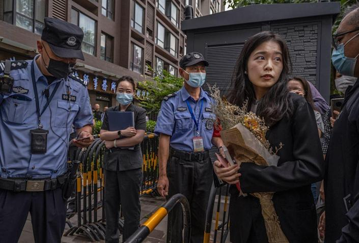 Leading figure in China's #MeToo movement Zhou Xiaoxuan, right, waits as her identification is checked by police before entering the Haidian District People's Court for a hearing in her case against prominent television host Zhu Jun, September 14, 2021 in Beijing, China. / Credit: Kevin Frayer/Getty
