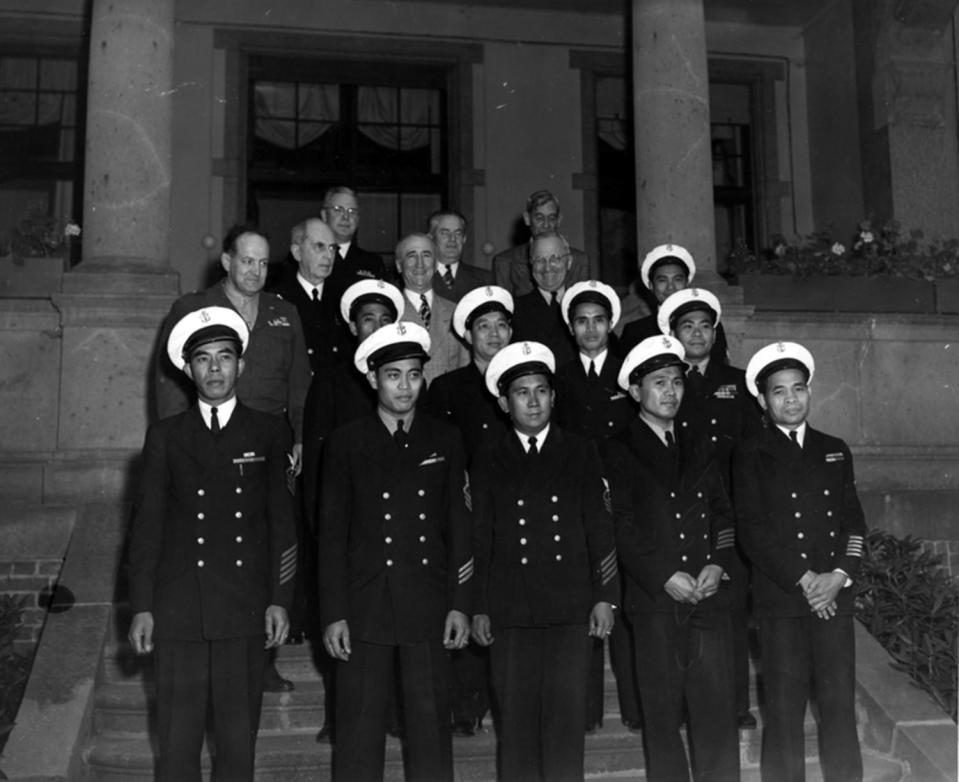 In this Aug. 1, 1945 photo, provided by the President Truman Library, President Harry S. Truman, in the third row, second from right, stands with members of his party and unidentified Filipino stewards during the Potsdam conference in Germany. Asian Americans, veterans and civilians in the U.S. and the Philippines are campaigning to name a Navy warship for a Filipino sailor who bravely rescued two crew members when their ship caught fire more than century ago, earning him a prestigious and rare Medal of Honor. (President Truman Library via AP)