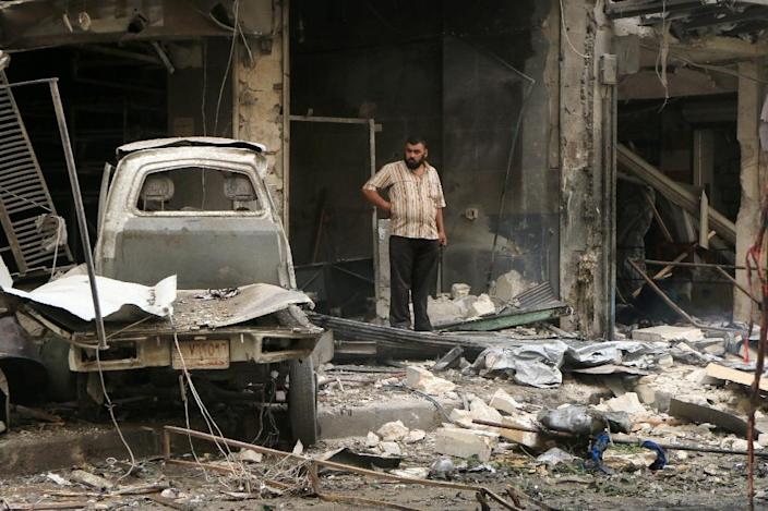 A Syrian man stands on a street amid the rubble of collapsed building following reported bombings by government forces on the rebel held al-Shaar district in Aleppo, September 21, 2015 (AFP Photo/Fadi al-Halabi)