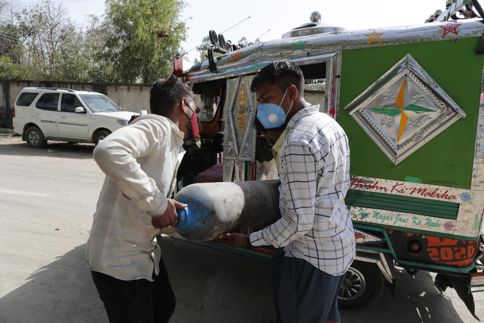People carry a medical oxygen cylinder at a charging station on the outskirts of Prayagraj, India, Friday, April 23, 2021. India put oxygen tankers on special express trains as major hospitals in New Delhi on Friday begged on social media for more supplies to save COVID-19 patients who are struggling to breathe. India's underfunded health system is tattering as the world's worst coronavirus surge wears out the nation, which set another global record in daily infections for a second straight day with 332,730. (AP Photo/Rajesh Kumar Singh)