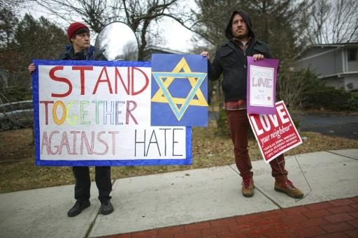 People hold signs of support near the house of Rabbi Chaim Rottenberg in Monsey, New York after the latest attack against Jewish targets
