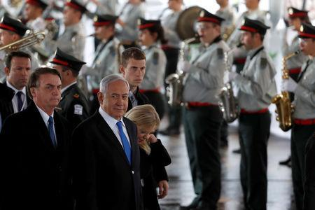 Brazilian President Jair Bolsonaro stands next to Israeli Prime Minister Benjamin Netanyahu and his wife Sara, as the Israeli military band perform during a welcoming ceremony upon his arrival in Israel, at Ben Gurion International airport in Lod, near Tel Aviv, Israel March 31, 2019. REUTERS/Ronen Zvulun