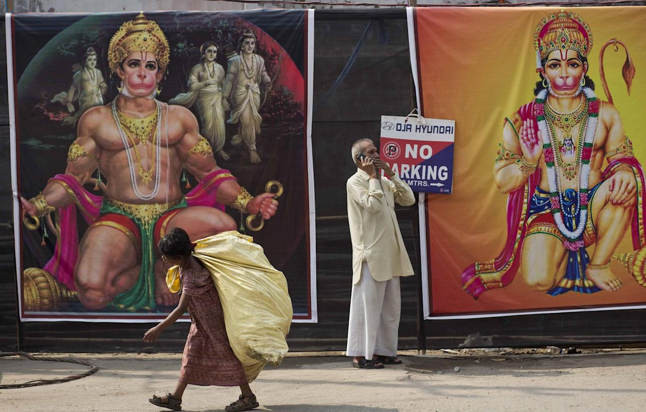 <p>An Indian rag picker girl walks past pictures of Hindu god Hanuman displayed by a street as a man talks on his mobile phone in Gauhati, India, Wednesday, April 12, 2017. Hanuman Jayanti, the festival that marks the birthday of Hanuman was celebrated by devotees on Tuesday. (AP Photo/Anupam Nath) </p>