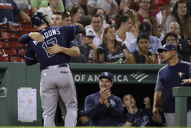 Tampa Bay Rays' Austin Meadows gets a hug at the dugout after his solo home run in the ninth inning of a baseball game against the Boston Red Sox at Fenway Park, Thursday, Aug. 1, 2019, in Boston. (AP Photo/Elise Amendola)