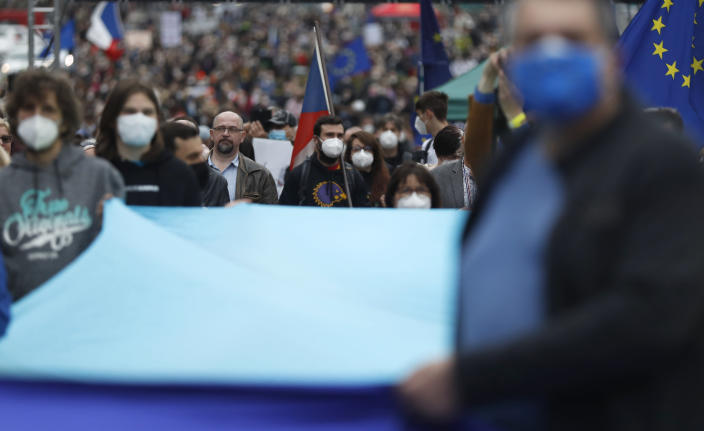 People attend a demonstration in Prague, Czech Republic, Thursday, April 29, 2021. Thousands of Czechs have rallied in the capital against President Milos Zeman, accusing him of treason for his pro-Russian stance over the alleged participance of Russian spies in a Czech huge ammunition explosion. (AP Photo/Petr David Josek)