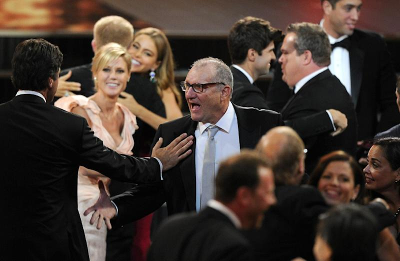 "Ed O'Neill, center, and Julie Bowen, second left, and the rest of the cast and crew of ""Modern Family"" stand to accept the award for outstanding comedy series at the 65th Primetime Emmy Awards at Nokia Theatre on Sunday Sept. 22, 2013, in Los Angeles. (Photo by Chris Pizzello/Invision/AP)"