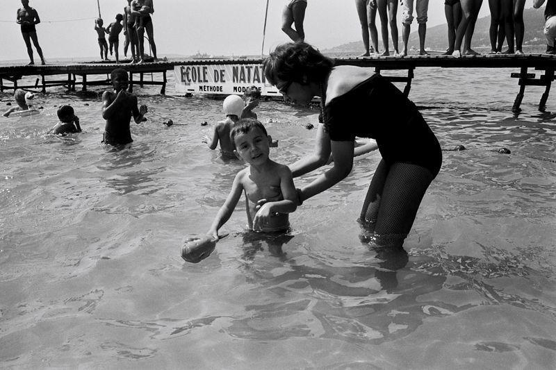 <p>Josephine Baker swims with one of her children in the ocean while on holiday in France in 1964.</p>