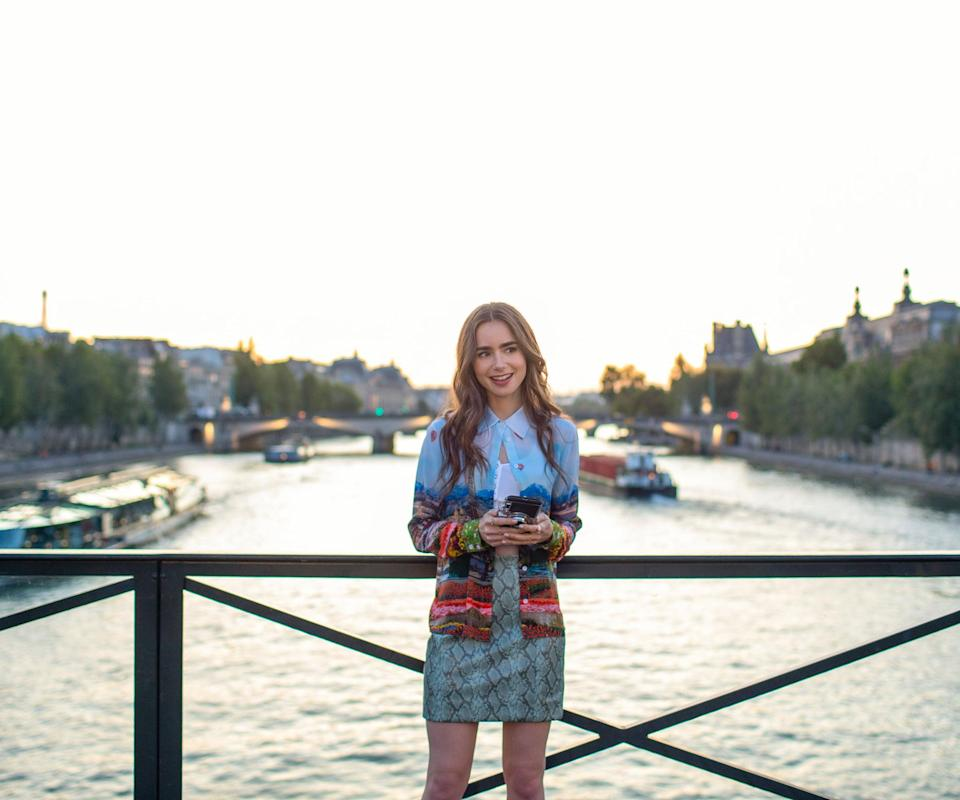 """<h2>Episode 1: """"Emily In Paris""""</h2><br><strong>What Emily's Up To:</strong> Emily gets transferred to work in the Paris office of her marketing company Savoir. She's thrilled for a chance at living life like the Parisians do — or like how she thinks they do.<br><br><strong>Where Emily Goes: </strong>Her trip to Paris begins with a montage of all the major landmarks: the Eiffel Tower, the Arc de Triomphe, the L'Assemblee Nationale, etc. Then she heads to her new home located in the Place de l'Estrapade square. She quickly establishes a routine in her neighbourhood like frequenting the local bakery <a href=""""https://www.yelp.com/biz/boulangerie-moderne-paris-7"""" rel=""""nofollow noopener"""" target=""""_blank"""" data-ylk=""""slk:Boulangerie Moderne"""" class=""""link rapid-noclick-resp"""">Boulangerie Moderne</a> for a delicious chocolate croissant. <br><br>She also establishes a routine near her office, which is above the <a href=""""http://www.galeriefourtin.com/content/presentation"""" rel=""""nofollow noopener"""" target=""""_blank"""" data-ylk=""""slk:Galerie Patrick Fourtin"""" class=""""link rapid-noclick-resp"""">Galerie Patrick Fourtin</a>. She eats lunch in a nearby park called <a href=""""https://www.lonelyplanet.com/france/paris/attractions/jardin-du-palais-royal/a/poi-sig/372471/359279"""" rel=""""nofollow noopener"""" target=""""_blank"""" data-ylk=""""slk:Jardin Du Palais Royale"""" class=""""link rapid-noclick-resp"""">Jardin Du Palais Royale</a>, where she meets Mindy (Ashley Park) a nanny who takes her under her wing to teach Emily all about Paris.<br><br>Of course, her first day in Paris wouldn't be complete without a visit to the Pont Des Arts — otherwise known as the famous lock bridge where lovers pledge themselves to each other by placing a padlock on the fencing. <br><br>Emily also checks out a waterfront café called <a href=""""https://lefloreenlile.fr/en/"""" rel=""""nofollow noopener"""" target=""""_blank"""" data-ylk=""""slk:Le Flore En L'ile"""" class=""""link rapid-noclick-resp"""">Le Flore En L'ile</a> which is famous for its ice cream.<span class="""""""