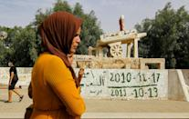 A woman walks past the sculpture of Mohamed Bouazizi's cart in the square named after him in central Sidi Bouzid (AFP/ANIS MILI)