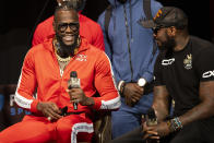 Deontay Wilder, left, speaks to his trainer, Malik Scott, during a news conference in advance of his heavyweight title boxing bout against Tyson Fury, in Las Vegas on Wednesday, Oct. 6, 2021. (Erik Verduzco/Las Vegas Review-Journal via AP)