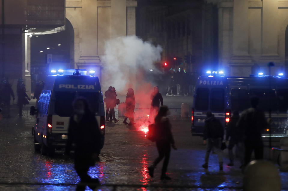 Police officers stand by burning flares during a protest against the government restriction measures to curb the spread of COVID-19, in Rome Tuesday, Oct. 27, 2020. Italy's leader, Premier Giuseppe Conte, has imposed at least a month of new restrictions to fight rising coronavirus infections, shutting down gyms, pools and movie theaters and putting an early curfew on cafes and restaurants. (AP Photo/Alessandra Tarantino)