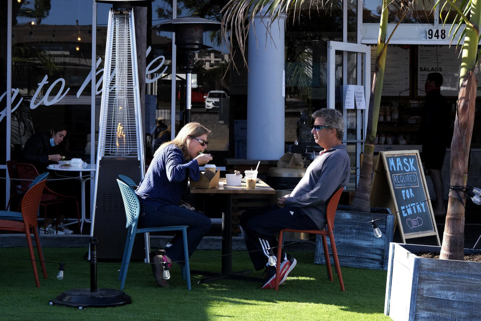 Patrons dine outside of a restaurant along the Coast Highway 101 in Encinitas, Calif., on Friday, Dec. 18, 2020. (AP Photo/Ringo H.W. Chiu)