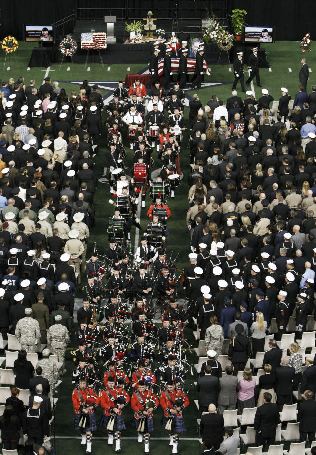 Bagpipers proceed Christopher Kyle's casket during the recession of a memorial service at Cowboys Stadium, Monday, Feb. 11, 2013, in Arlington, Texas. Thousands attended the public memorial service for Kyle, the former Navy SEAL sniper who was shot to death at a Texas shooting range. (AP Photo/Brandon Wade)