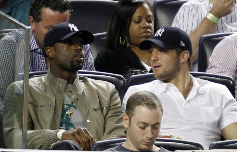 Miami Heat's Dwayne Wade, left, sits beside New York Jets quarterback Tim Tebow during the New York Yankees' baseball game against the Los Angeles Angels at Yankee Stadium in New York, Sunday, April 15, 2012. (AP Photo/Kathy Willens)