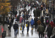 People walk along Buchanan Street in Glasgow, Scotland, Tuesday Nov. 17, 2020. 11 local authorities in Scotland, including Glasgow, are to be placed into its highest tier of coronavirus restrictions this week. The restrictions, which are similar to the lockdown in England, are set to run from Friday until Dec. 11. (Andrew Milligan/PA via AP)