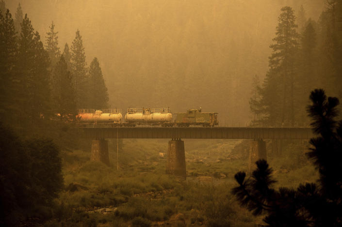 A fire train crosses a bridge as the Dixie Fire burns in Plumas County, Calif., on Saturday, July 24, 2021. The train is capable of spraying retardant to coat tracks and surrounding land. (AP Photo/Noah Berger)