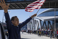 "Hailun Song waves a U.S. flag and cheers marchers as a ""stop Asian hate"" rally in downtown Atlanta passes by Saturday afternoon, March 20, 2021. (AP Photo/Ben Gray)"