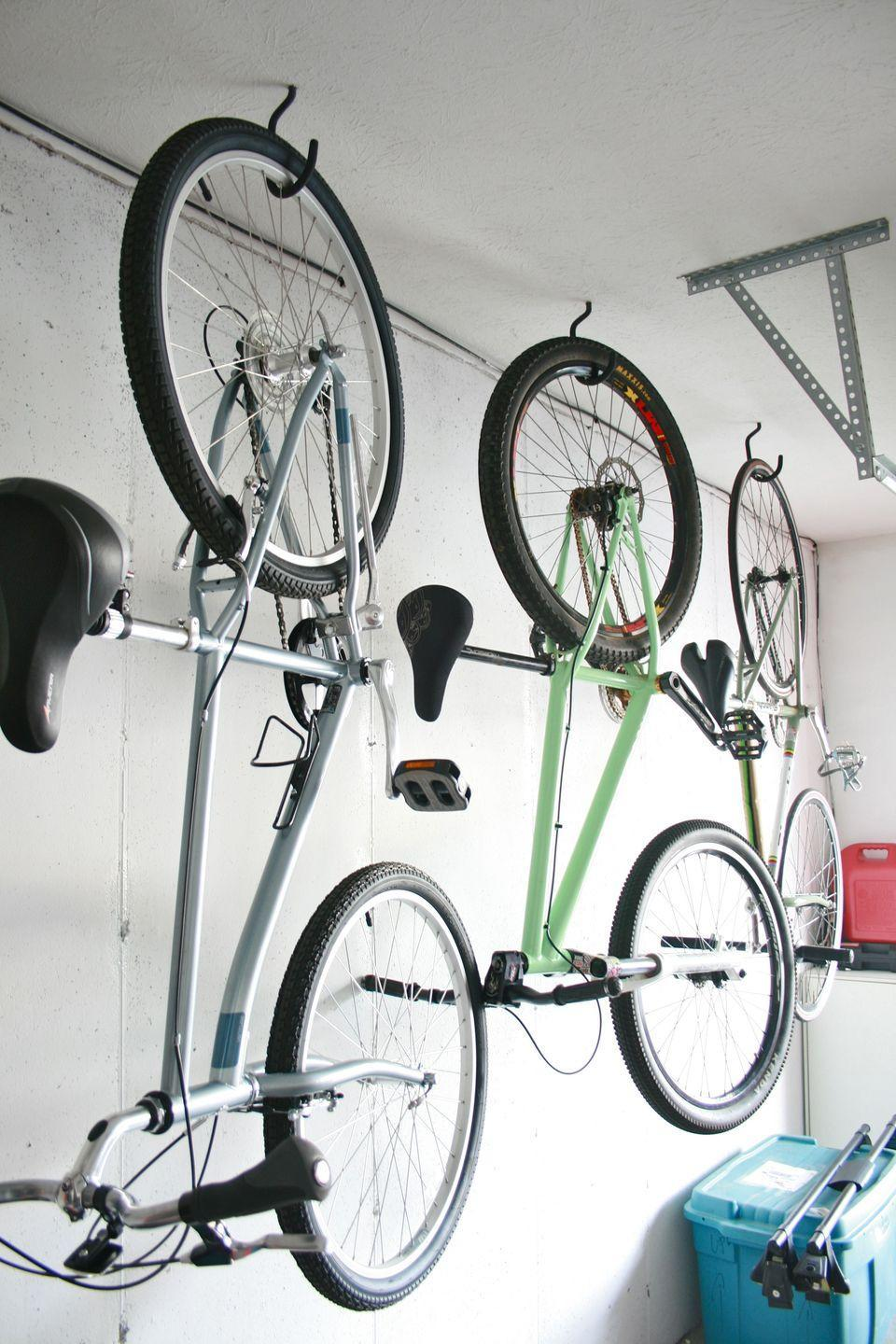 """<p>There are perhaps no other items that make a mess out of garages the way bicycles do. Get them off the floor and out of your way by hanging bike hooks from your ceiling. Just make sure you screw the hook into a stud for maximum strength.</p><p><strong>Get the tutorial at <a href=""""https://www.dreamgreendiy.com/2012/11/30/hang-bikes-in-the-garage-check/"""" rel=""""nofollow noopener"""" target=""""_blank"""" data-ylk=""""slk:Dream Green DIY"""" class=""""link rapid-noclick-resp"""">Dream Green DIY</a>.</strong></p><p><a class=""""link rapid-noclick-resp"""" href=""""https://www.amazon.com/Impresa-Products-4-Pack-Bike-Hanger/dp/B01CZ7WZ08/ref=sr_1_3_sspa?tag=syn-yahoo-20&ascsubtag=%5Bartid%7C10050.g.36449426%5Bsrc%7Cyahoo-us"""" rel=""""nofollow noopener"""" target=""""_blank"""" data-ylk=""""slk:SHOP BIKE HOOKS"""">SHOP BIKE HOOKS</a><br></p>"""