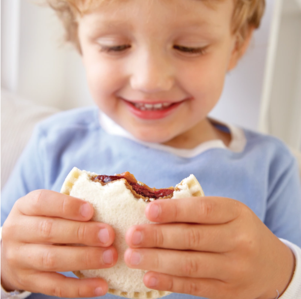 A young boy holds an Uncrustables sandwich. (Source: J.M. Smucker Company)