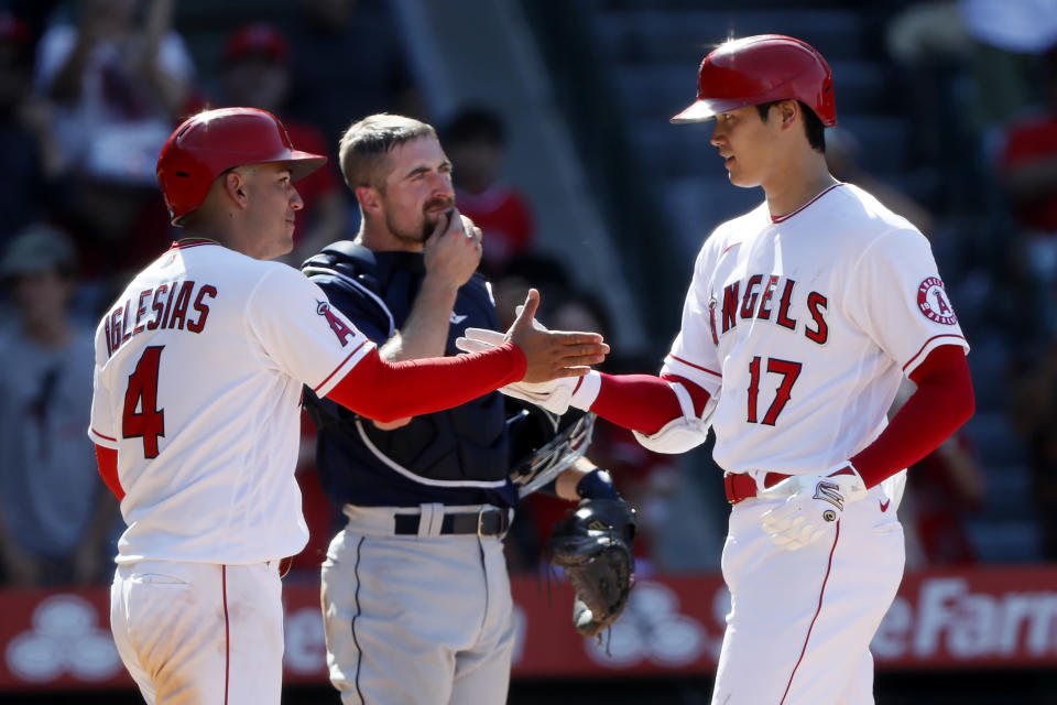 Los Angeles Angels' Jose Iglesias, left, congratulates Shohei Ohtani, who hit a two-run home run, next to Seattle Mariners catcher Tom Murphy during the ninth inning of a baseball game in Anaheim, Calif., Sunday, July 18, 2021. (AP Photo/Alex Gallardo)