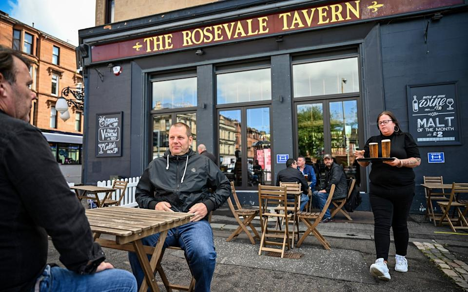 Beer gardens have been allowed to reopen in Scotland from today. Here's members of the public enjoying their first beers since March in Glasgow - Getty Images Europe